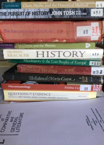 A pile of academic books and papers on a desk