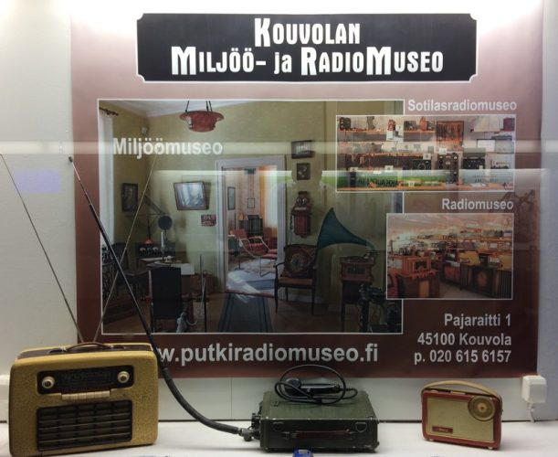 Display case for the Miljöö museum and radio museum in Kouvola railway station, Finland. Three radios displayed in front of a poster for the museums.