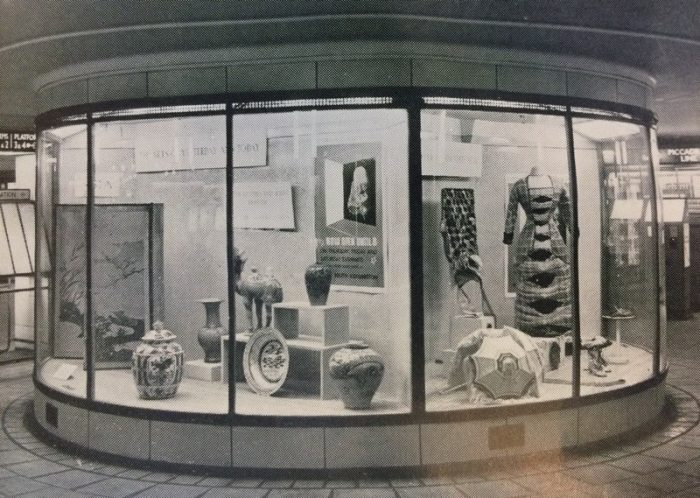 A museum display case in the rotunda in the ticket hall at Leicester Square tube station. Two cases show museum objects and signs
