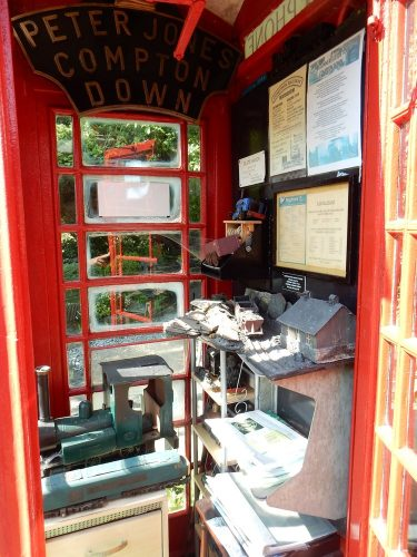 Compton Down Railway Museum interior. Signs, train models and other objects inside an old BT phone box